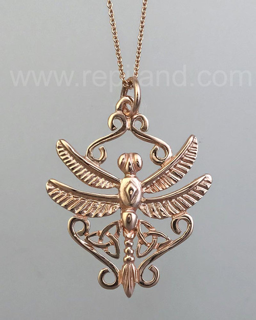 A dragonfly with trinity knots and scrollwork. Rose gold.