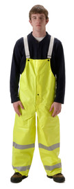 Nasco Omega FR Yellow Rain Overall - Young Man wearing a NASCO yellow rain bib overall with 2 reflective tape around each leg below the knee