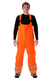 Nasco Omega FR Class 3 Orange Rain Bib Overall - Young Man wearing a NASCO black shirt and orange rain bib overalls with straps and reflective tape below the knees