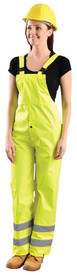 Occunomix Class E Adjustable Leg Cuff Bib Rain Pants - Front view of  woman wearing Occunomix yellow high visibility rain bib overalls with adjustable suspenders and 2 silver reflective tape placed below the knees.
