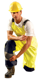 Occunomix Class E Hi Viz Waterproof Bib Pants - Front view of  man wearing Occunomix yellow high visibility rain bib overalls with adjustable suspenders and 2 silver reflective tape placed below the knees.