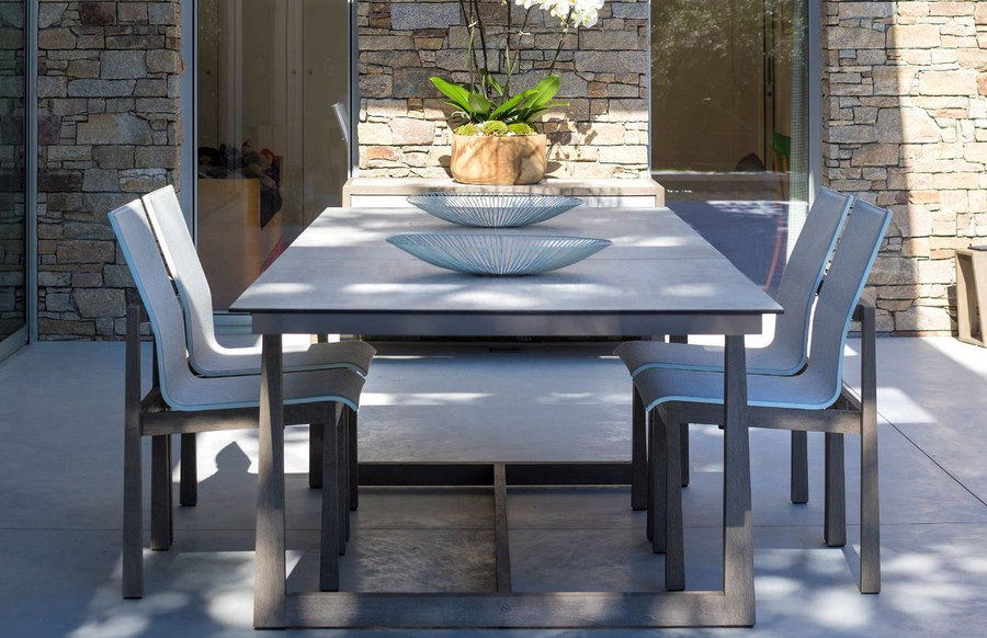 End view of Les Jardins outdoor teak table with HPL top and matching Skaal dining chairs with Batyline Eden mesh