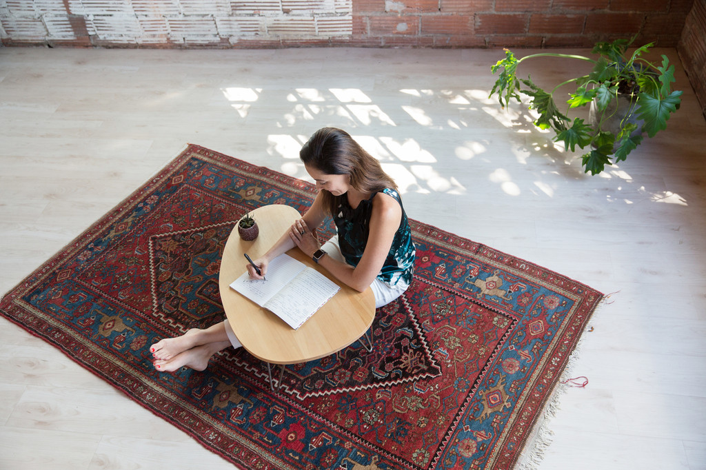 Woman writing at Elizabeth Floor Desk with legs outstretched