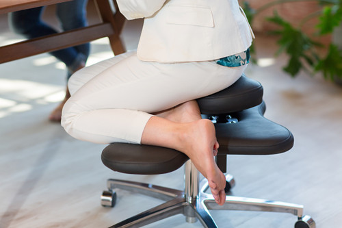 Woman sitting barefoot on Soul Seat chair for cross legged sitting