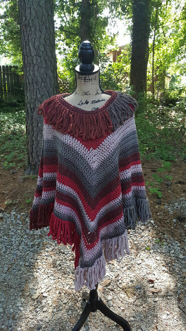 Classic poncho style. Colors are burgundy, grays, reds, very muted. The fringe is crochet chains looped together so they won't fray over time. 100% acrylic. Machine was delicate, tumble low dry.