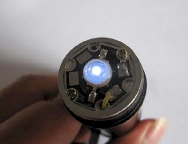 Top view of the super single ultra violet LED flashlight head. The LED is on showing the circuit board.