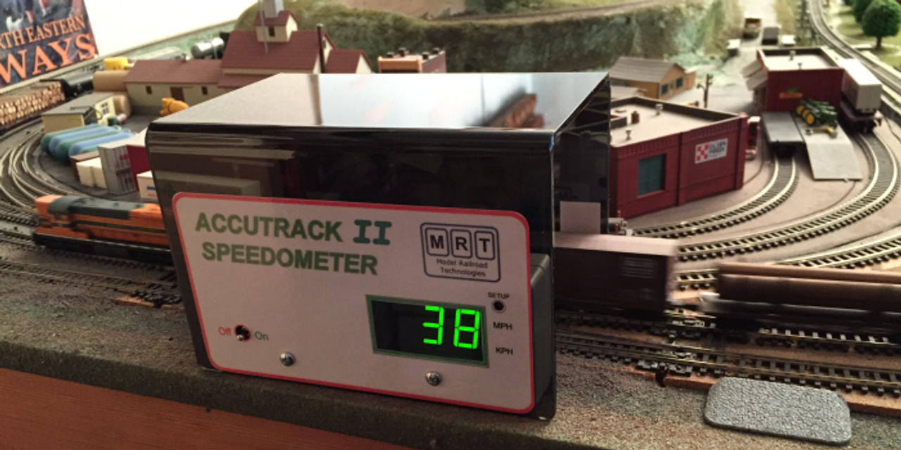Accutrak II Speedometer by MRT Introducing the Accutrack II Model Train Speedometer  Note:  This is a portable, stand-alone speed detection device.  It works with DC or DCC layouts.  It works with any DCC system since they are not connected in any way.  Model Railroad Technologies is please to announce the development of the Accutrack II Speedometer for measuring scale speeds of model railroad locomotives and trains. The Accutrack II includes several features not present in the original Accutrack Speedometer.  We have listened to customer and dealer input and have incorporated the most desired new features and functions. Although several small changes have been made in the nearly 10 years that the Accutrack has been on the market, no major redesign has been done up until now.  These new features include: Clearance for HO scale AutoMax cars and double stacks with high box containers. Several modelers running modern equipment could not run their AutoMax equipped trains through the existing model. With the Accutrack II they can! (see photo). The addition of OO (4mm) and N Gauge (9mm) to the existing HO (1:87) and N scale (1:160) settings. The addition of Kilometers per hour (KPH) as a unit of measure for all included scales.  Scale selection includes the ability to select each of the included scales with measurement displayed in either miles per hour (MPH) or kilometers per hour (KPH). Display resolution is:  •.1 mph/kph up to 10 •1 mph/kph for 10 and above Adjustable automatic Power Down time. Originally limited to powering down after 5 minutes of no train activity, this time period is now adjustable from 1 minute to 30 minutes. The power down feature can also be disabled completely, if desired, but re-enabled as desired. We believer that these new features, coupled with the simple, no installation setup of the original Accutrack, will add to the enjoyment of serious model railroaders, whatever their interest.  Model Railroad Technologies Accutrack Speedometer   The M