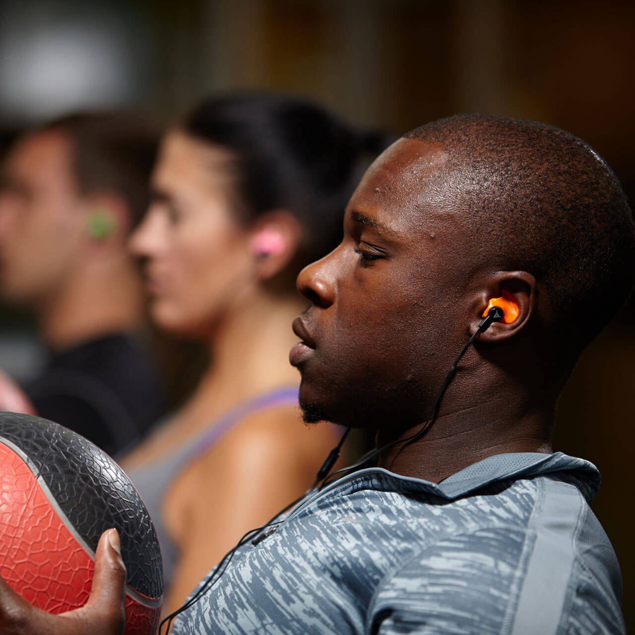 man working out with orange decibullz headphones