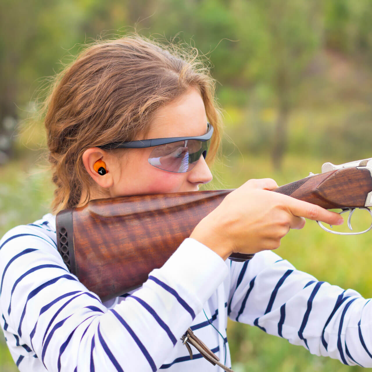 woman sport shooting with orange decibullz hearing protection
