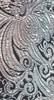 Tessuto brillante con marcato effetto di chiaroscuro con disegni opachi su fondo lucido (raso).