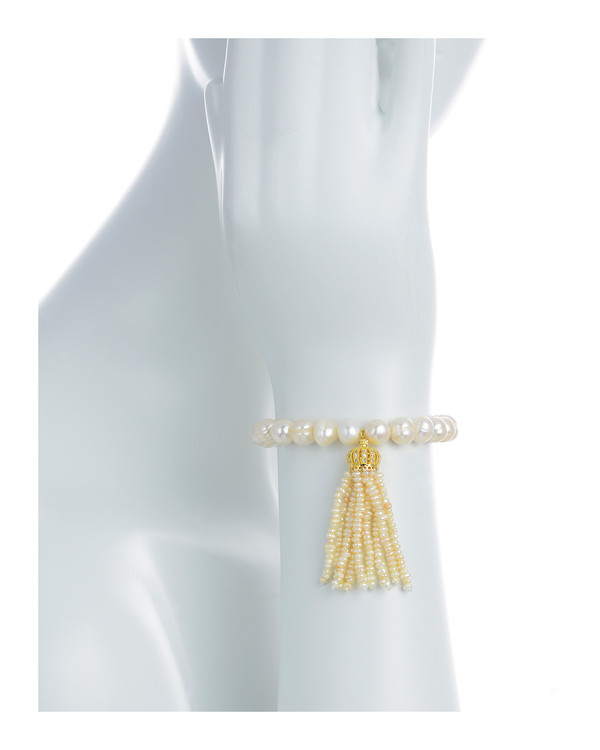 """Little Gold Crown - Pearl Bracelet on model: Single strand beaded pearl bracelet with white freshwater pearls 9-10mm,1.5"""" seed pearl tassel drop suspended from mixed metal gold crown, on elastic, one size"""
