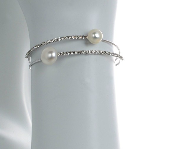 zoom on model, Rockefeller Center  Pearl bracelet: Double stranded mixed metal cuff bracelet featuring 2 freshwater pearls 8mm, with 2 rows of CZ accents, one size.