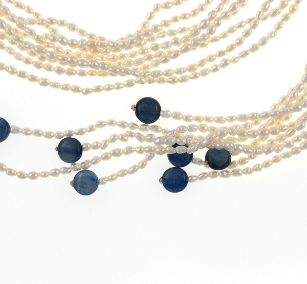 """Catedral de Mármol - Pearl Necklace, zoom on kyolite beads on necklace, 8-strands of white seed pearls, 3-4mm, individually hand-knotted on natural silk, finished with 8 kyolite beads at the ends and held together with a mixed-metal feather pendant hand set with CZ's at 32"""" in length."""
