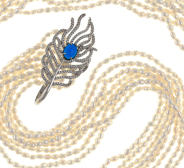 """Catedral de Mármol - Pearl Necklace, zoom on feather pendant on necklace, 8-strands of white seed pearls, 3-4mm, individually hand-knotted on natural silk, finished with 8 kyolite beads at the ends and held together with a mixed-metal feather pendant hand set with CZ's at 32"""" in length."""