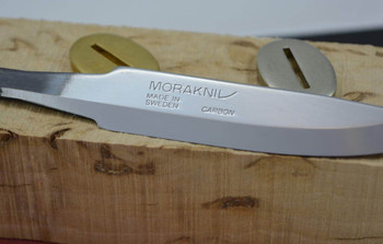 Close-up of Mora 75 blade in a kit with bolster and solid wooden handle block. This item for sale is the blade only, not the entire kit