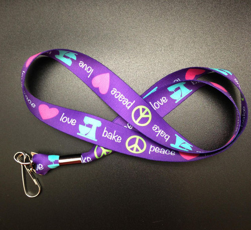 Peace, Love, Bake with with a blue mixer, lime peace sign and pink heart on a purple background features a J-Hook end for keys and ID cards.