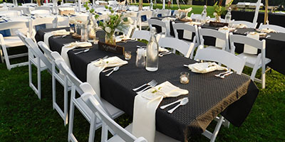 Tables and chairs set up for a wedding with tablecloths and vases