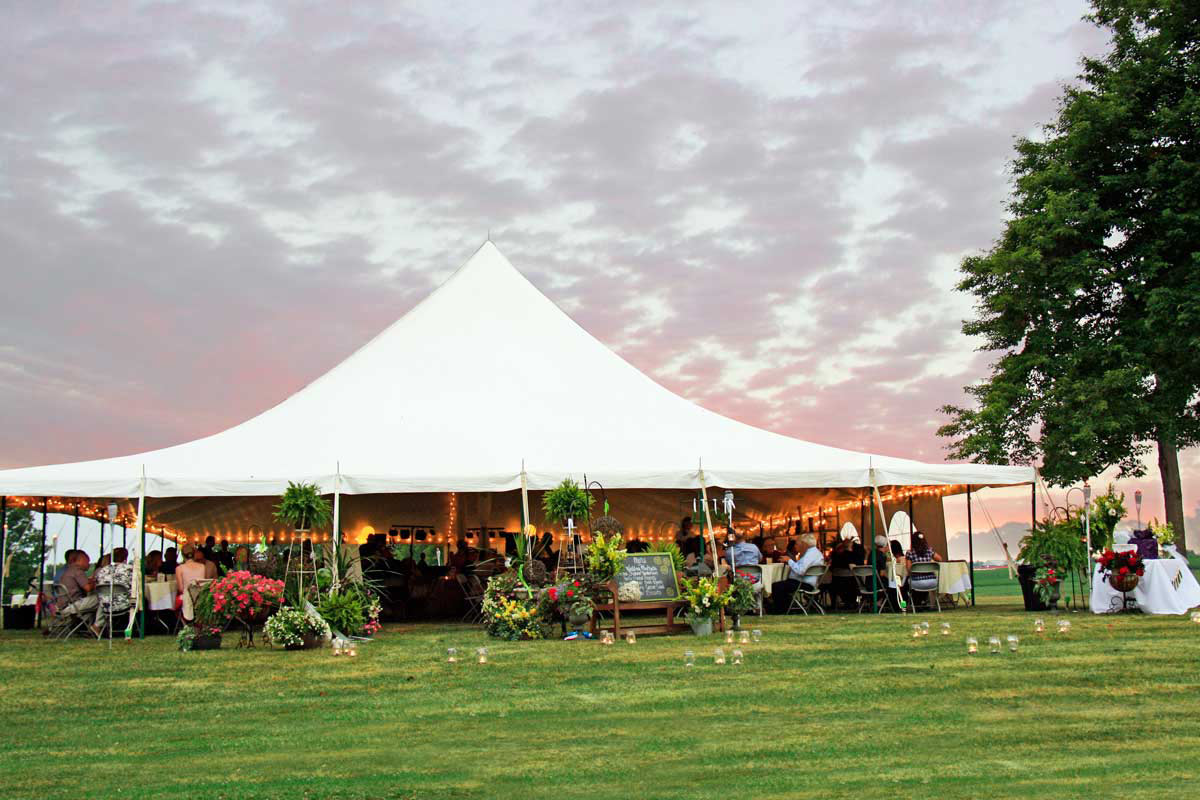 A warm pink sunset cast over a graduation party beneath a high peak tent decorated with florals