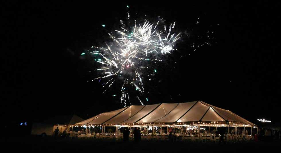 a clear top tent with fireworks in the sky and colorful lights on the tent