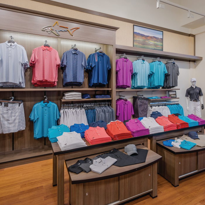 Selection of Greg Norman shirts on shelves and hanging