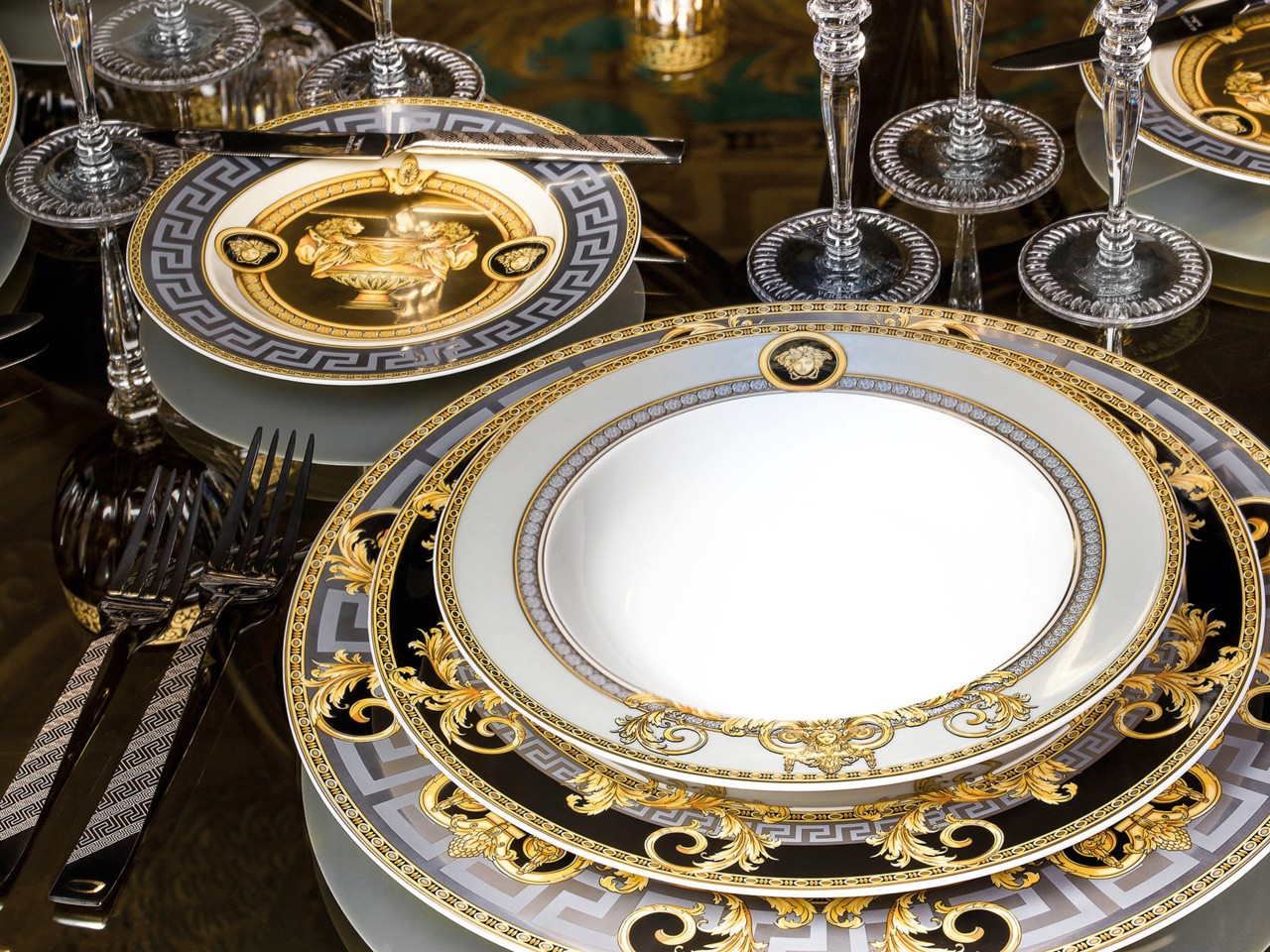 Versace Prestige Gala dinner table setting showing 3 stacked plates with side plate, Versace flatware and Versace stemware on dark polished table.